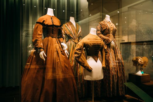 Through glass view of bright ornamental aged female dresses on mannequins on exhibition