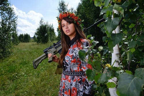 Young woman with assault rifle in countryside