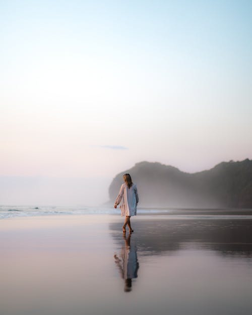Faceless woman walking on wet sandy beach in early morning
