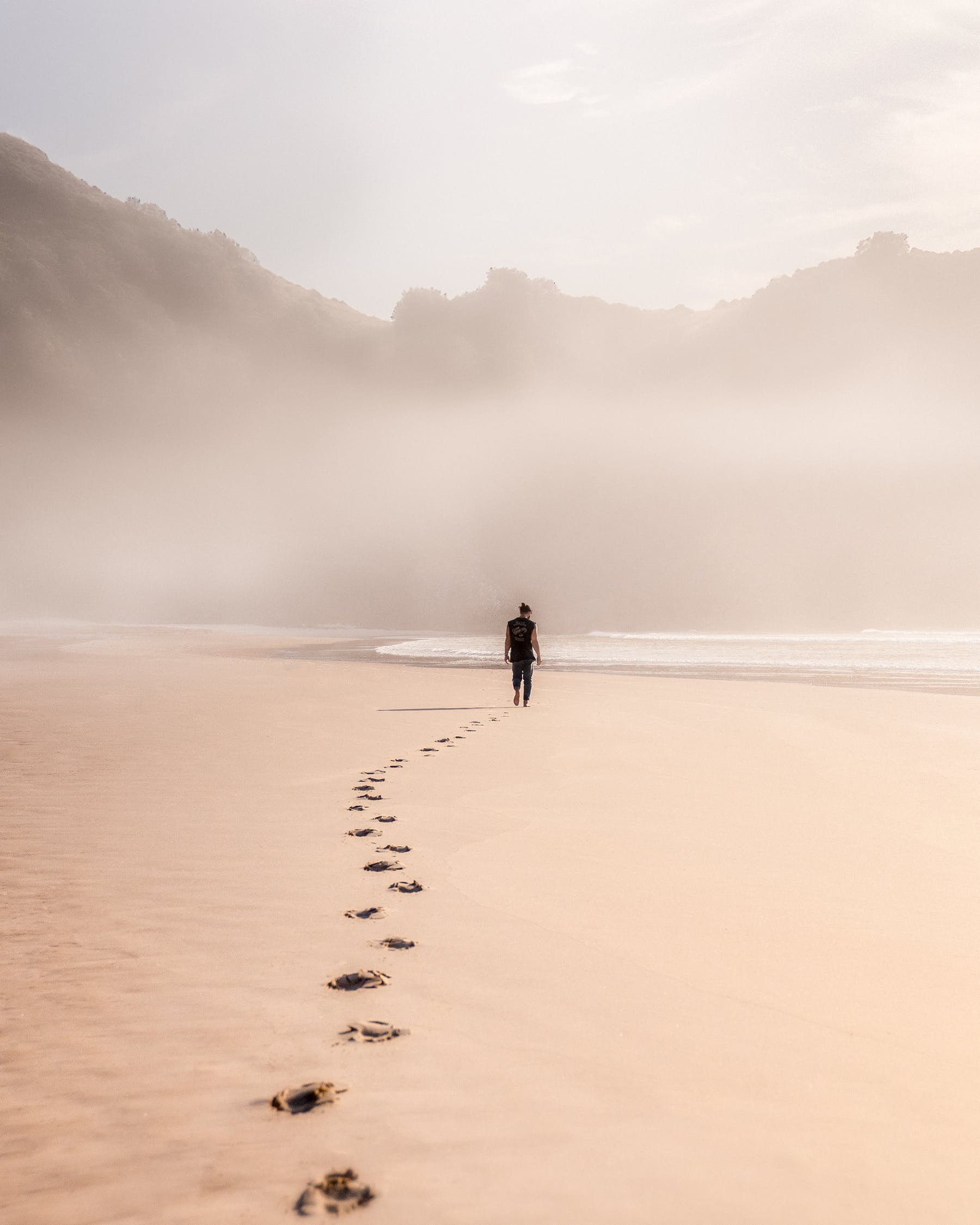 Back view full length male strolling on misty seacoast against rough cliffs and leaving footprints on sand