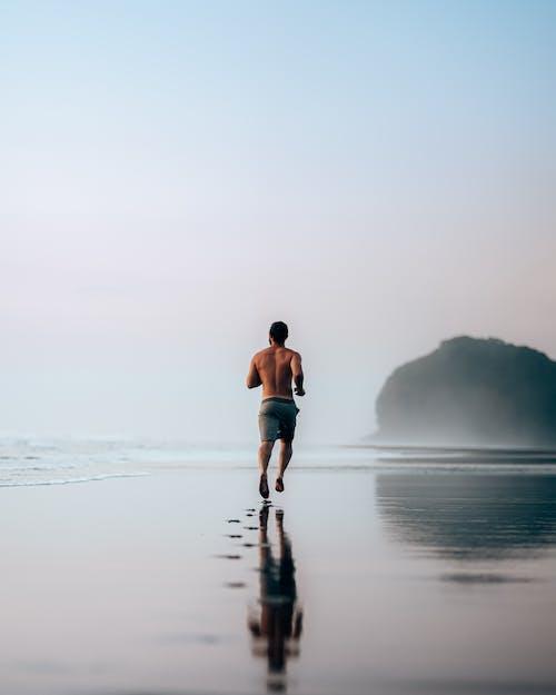 Gesichtsloser Muskulöser Mann, Der Auf Nasser Szenischer Küste Joggt