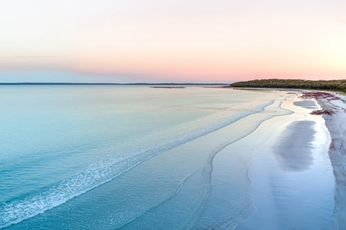 Spectacular view of serene sea with ripples on water near sandy beach at sundown