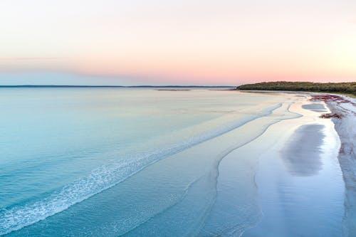在日落時波浪海洋附近的沙質海岸