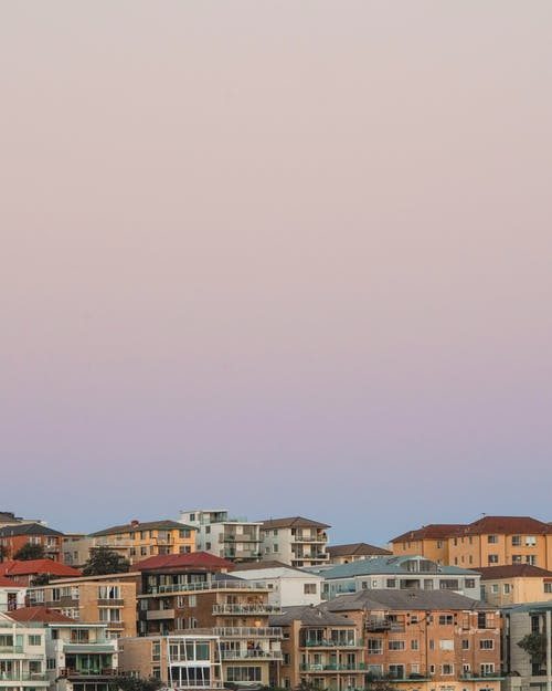 Old residential building facades under cloudless sky at sunset