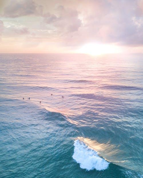 Unrecognizable tourists swimming in wavy ocean at sundown