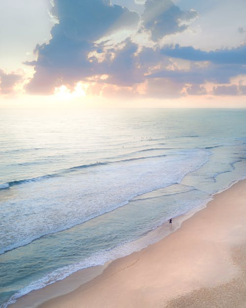 From above of unrecognizable tourist on sandy ocean coast under cloudy sky with shiny sunlight in evening