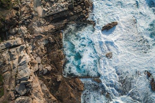 Rough rock near foamy sea in stormy weather