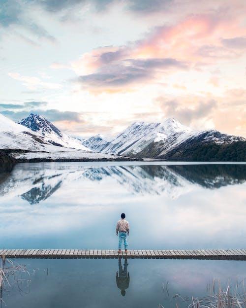Frau In Der Schwarzen Jacke, Die Auf Dock Nahe Schneebedecktem Berg Steht
