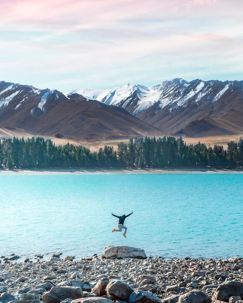 Back view of unrecognizable person jumping on rocky coast near calm turquoise river against mountains with snow in daytime
