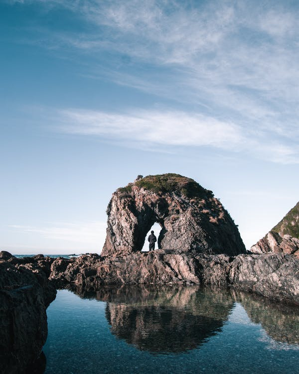 Back view of anonymous person standing in rocky arch near calm water against blue sky