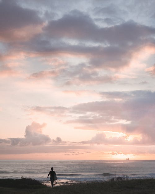 Silhouette of anonymous person walking on coast against wavy ocean under colorful sky at sunset