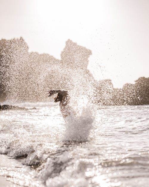 Anonymous person standing and splashing water in ocean with sandy beach in sunny day