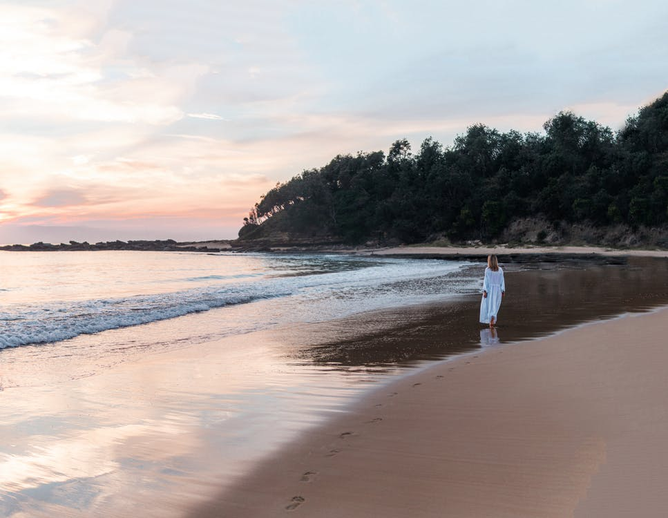 Back view of anonymous female in long white dress walking along empty sandy beach near calm ocean at sunset