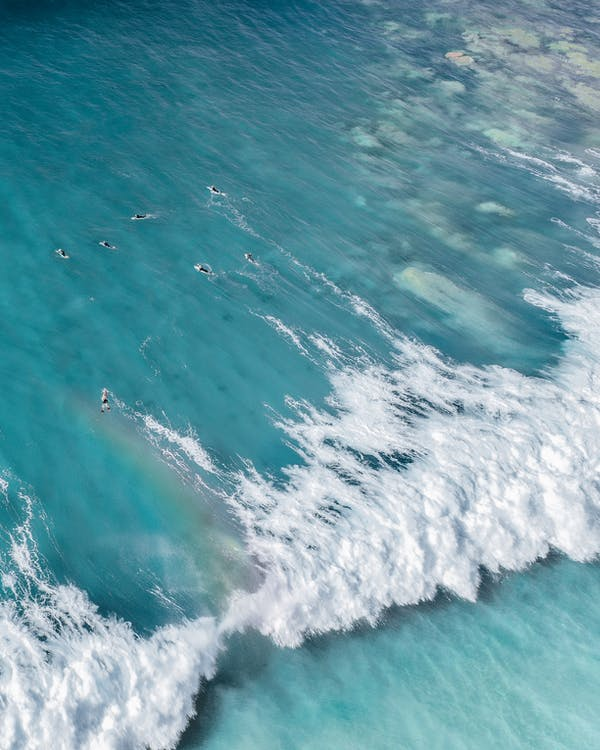 Aerial view of bright blue water of sea with foamy waves in sunny day