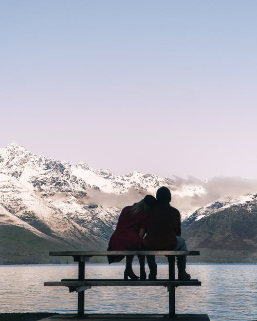 Romantic couple sitting on bench and admiring lake and mountains