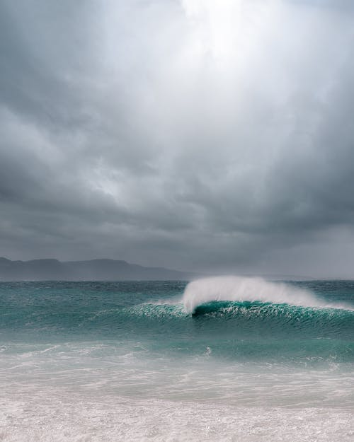 Blue ocean with foamy waves and sandy beach under gray cloudy sky in daytime