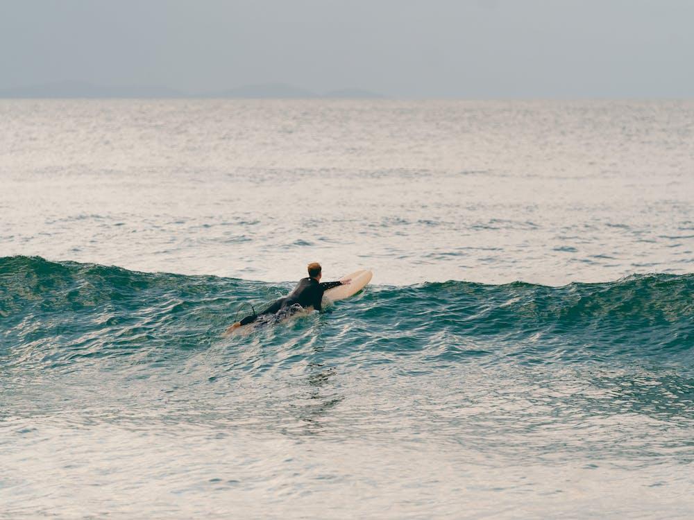 Man in Black Wetsuit Surfing on Sea Waves