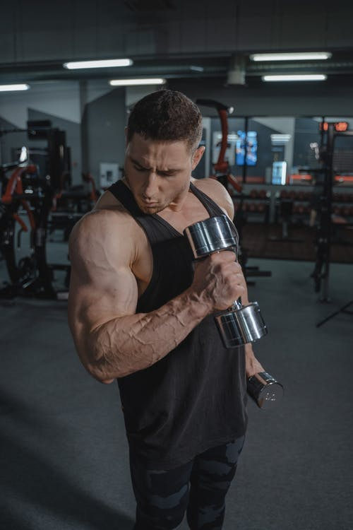 Man in Black Tank Top Holding Silver and Black Dumbbell