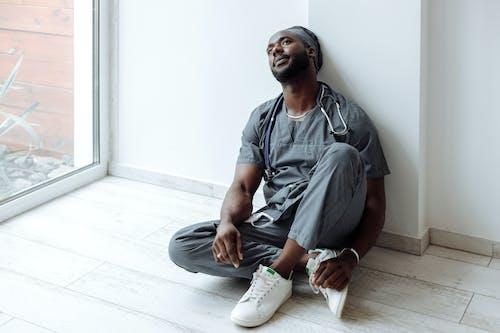 Người đàn ông Mặc áo Sơ Mi Màu Xám Cài Nút Ngồi Trên Sàn Nhà