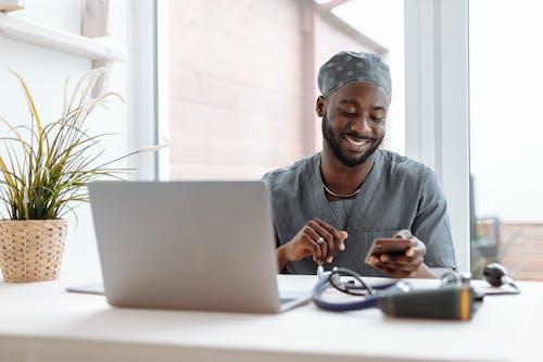 Người đàn ông Mặc áo Sơ Mi Xám Sử Dụng Macbook Màu Bạc