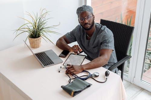 Người đàn ông Mặc áo Sơ Mi Màu Xám Cài Nút Ngồi Trên Ghế Trước Bàn Với Máy Tính Xách Tay