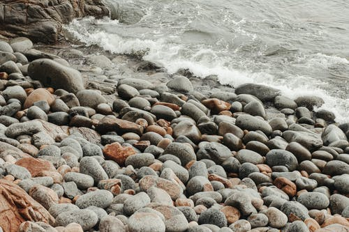 From above scenic view of stone shore near foamy rippled ocean in stormy weather