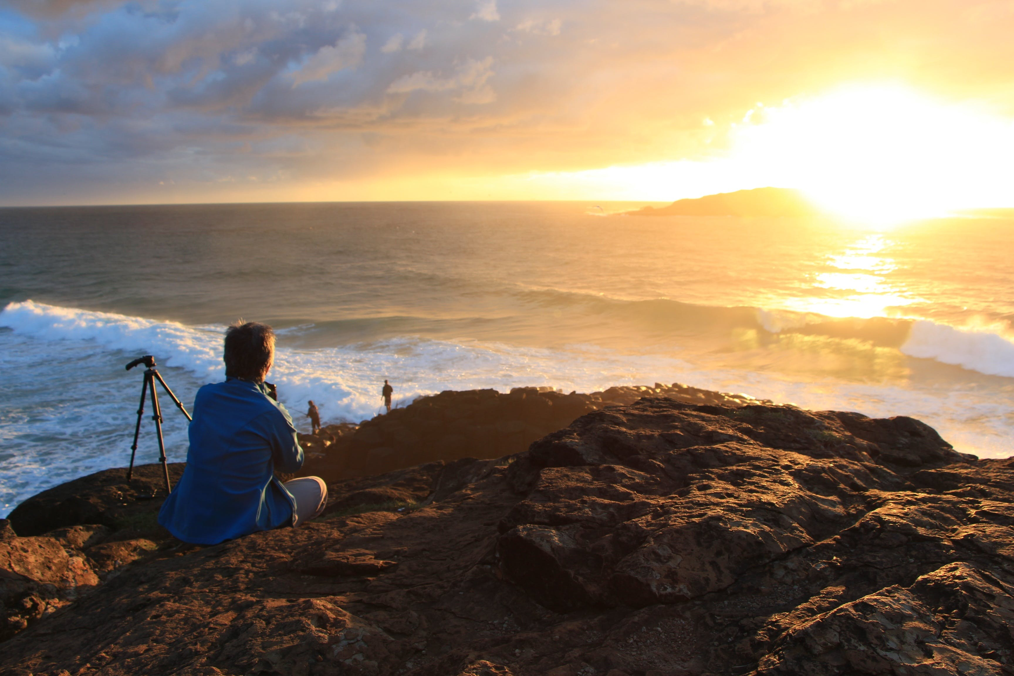 Person Sitting on Cliff Watching Sunset