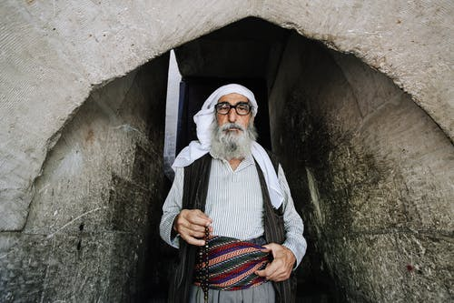 Bearded Muslim man in traditional apparel near aged temple