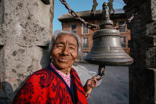 Cheerful elderly Hindu female in bright apparel touching aged temple campane and looking at camera on street