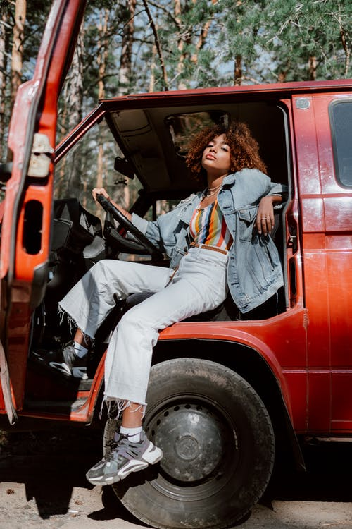 Woman in Blue Denim Jacket and White Pants Sitting on Red Car