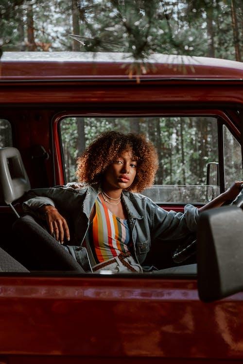 Woman in Blue Denim Jacket Sitting on Car Seat