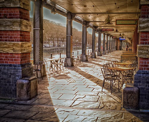 Foto profissional grátis de arquitetura, árvores, cadeiras, chão de pedra