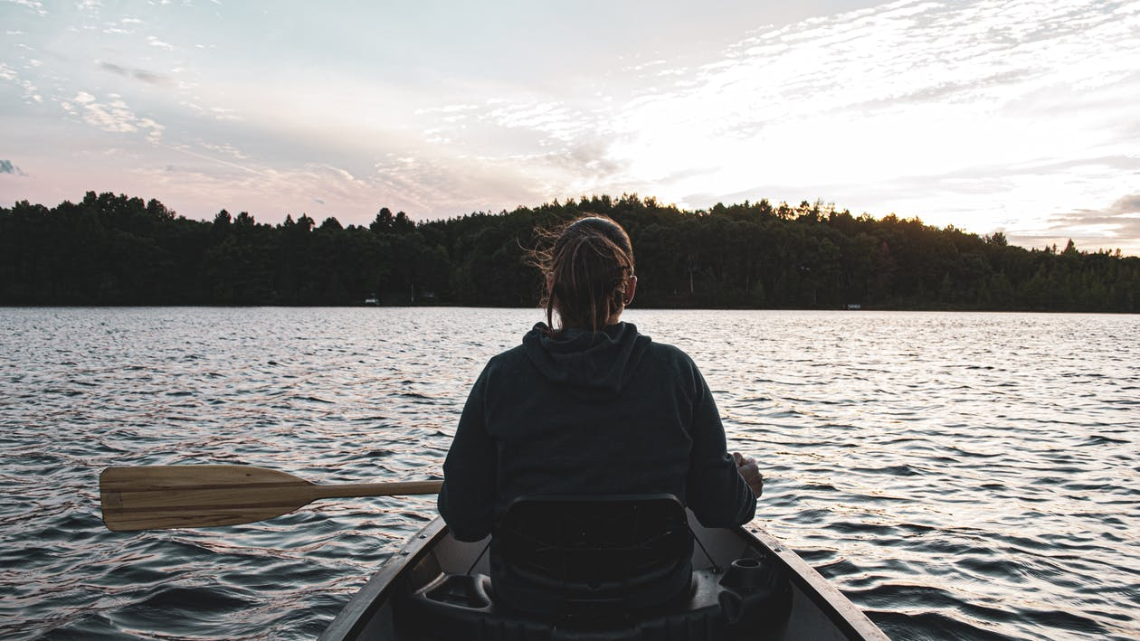 Man in Blue Hoodie Riding on Boat