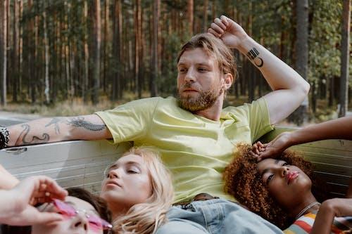Man in Yellow Polo Shirt Beside Woman in Gray Shirt