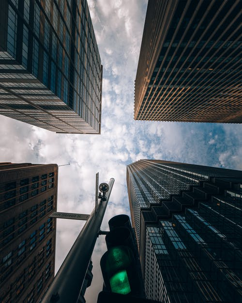 Low Angle Photography of High Rise Buildings Under White Clouds