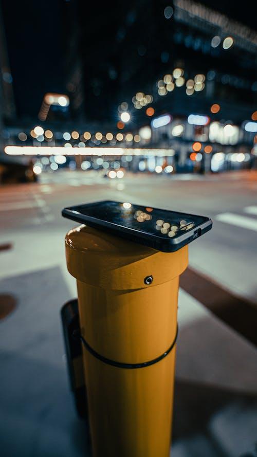 Black Iphone on Yellow Plastic Trash Bin