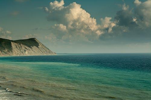 Rippled sea against mountain under cloudy sky
