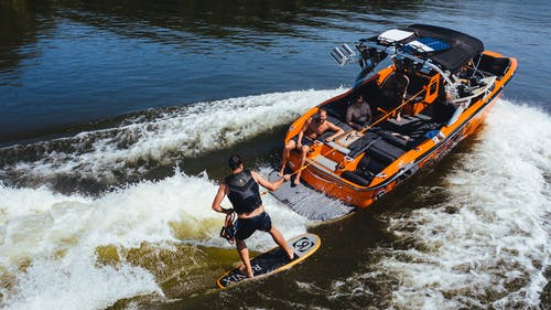 Anonymous athlete on wake board on river near motor boat