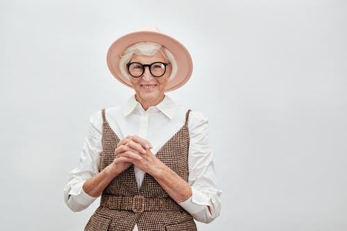 A Stylish Elderly Woman in Eyeglasses with Her Hands Together
