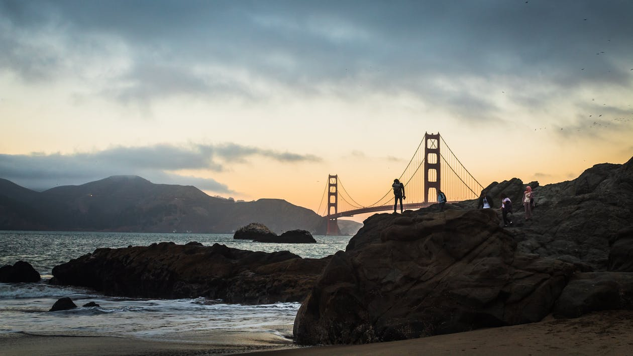 People on the Rocks with a Scenic View of the Golden Gate Bridge During Sunset