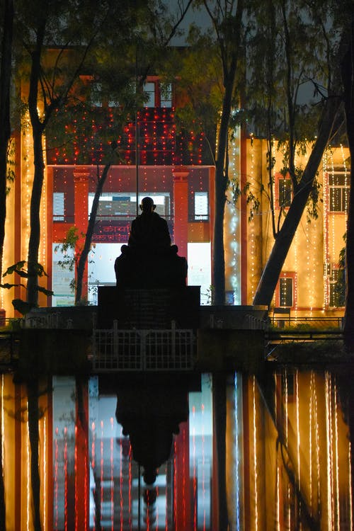 Silhouette of Man Sitting on Bench Near Body of Water during Sunset