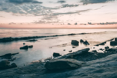 Scenery view of shore with rough stones against rippled ocean with horizon under cloudy sky at sundown