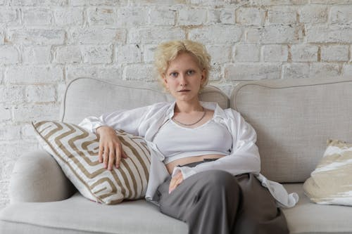 Charismatic woman relaxing on sofa at home