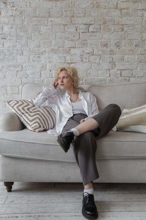 Pensive woman sitting on couch