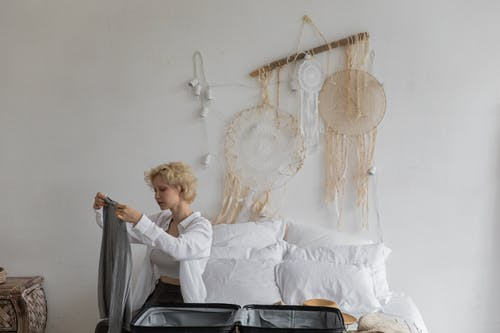 Calm woman packing luggage in bedroom