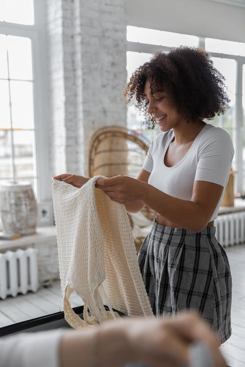 Side view of happy African American female putting dress in suitcase while packing luggage for trip in room with crop person