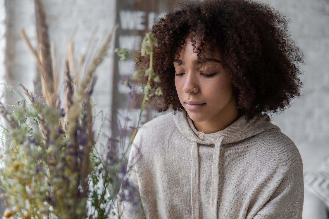 Thoughtful black woman near wildflowers