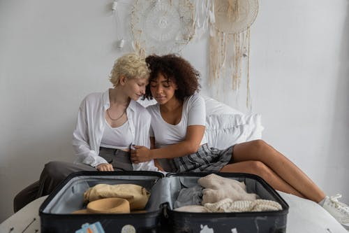 Diverse lesbian couple caressing on bed