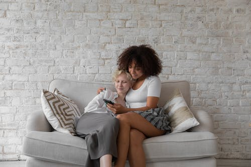 Lesbian couple surfing smartphone at home