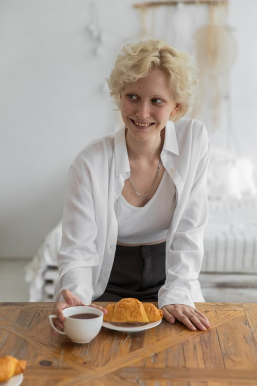 Happy attractive female in trendy outfit sitting at table with fresh croissant and cup of hot coffee while smiling and looking away